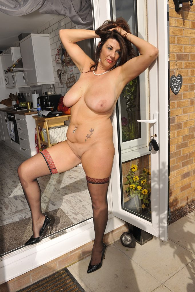Just look at this stunning, 100% natural woman standing on her backdoor step wearing just apair of black stockings and high heels and tell me she's not making your old boy hard.